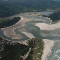 A view of the Sand Lake estuary from above. A large sandy area with a river running through it and opening into the ocean.