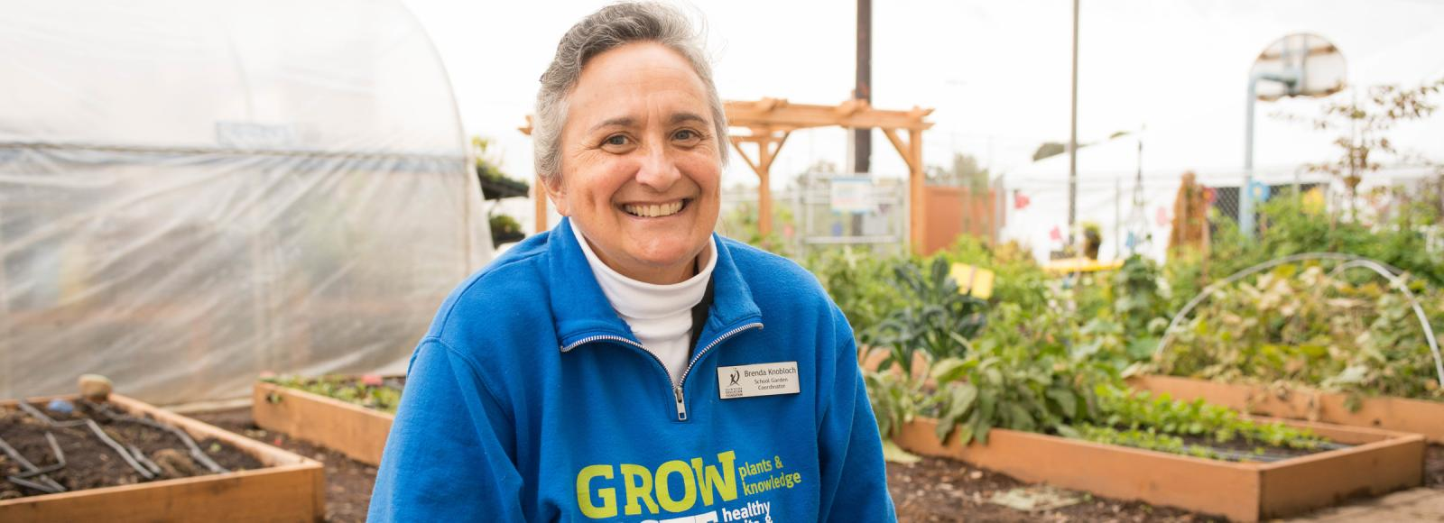 a woman sits on a bench inside a greenhouse wearing a bright blue sweatshirt that reads