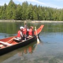 Antone Minthorn and others paddling a canoe with forested beach in background.