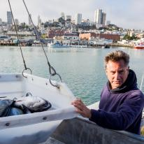 A man wearing a hoodie has his hand on a square bucket of fish. The bucket is suspended by wires. The sea, a marina, and a cityscape can be seen behind him.