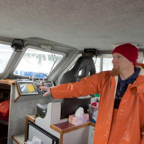 man in orange raincoat and waders with a red beard and stocking hat stands in a boat pointing to a computer screen