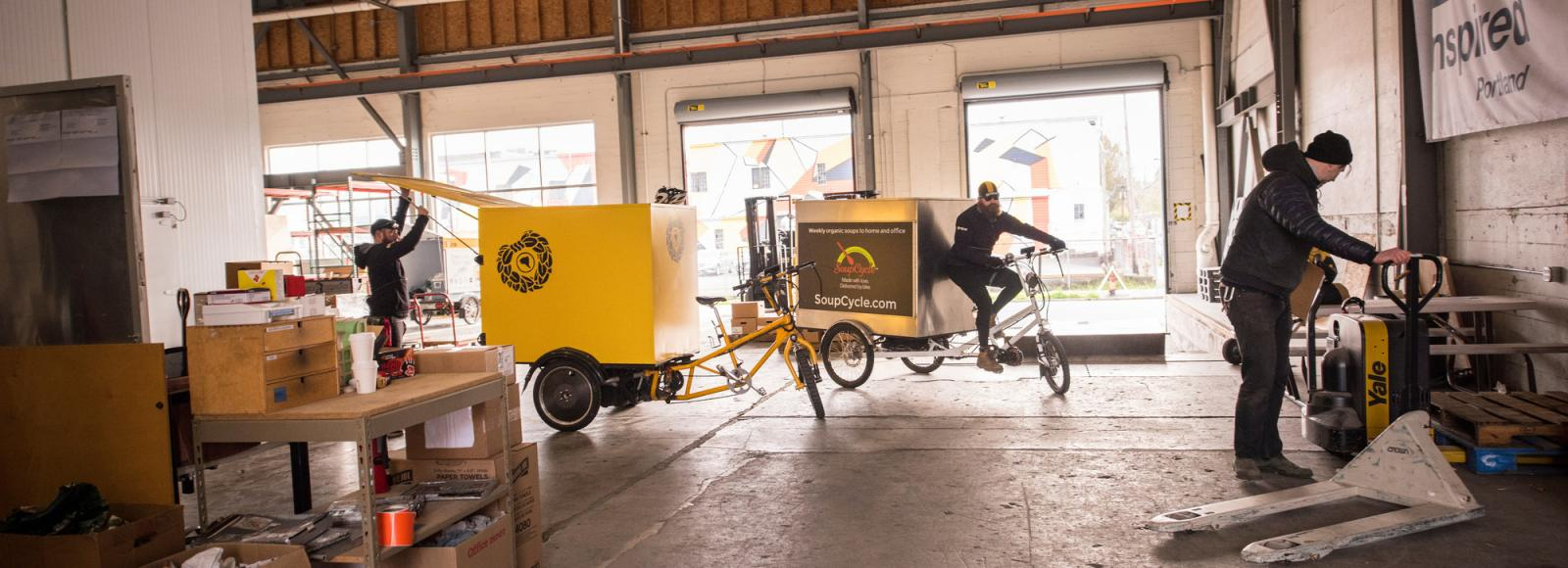 Two people inspect and ride bicycle trikes in a large warehouse.