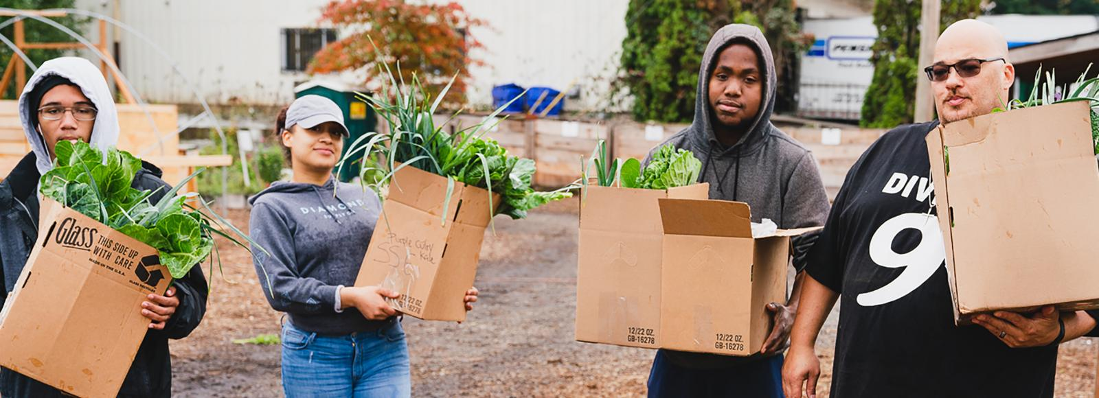 Three young people and their instructor hold cardboard boxes containing fresh green produce