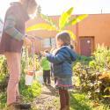 Gardener Suzanne Stone at New Day School in Portland hands a preschooler a pale for harvesting raspberries from the preschool garden.