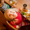 A preschooler looks straight up into the camera as she sits down for lunch. Her metal plate is full of colorful vegetables.