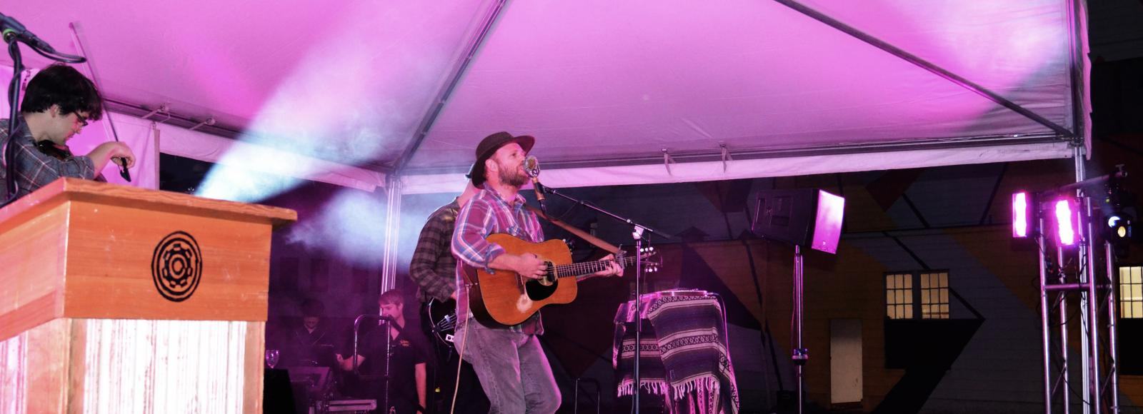 Man wearing plaid shirt and hat plays guitar on a pink-lit stage at night