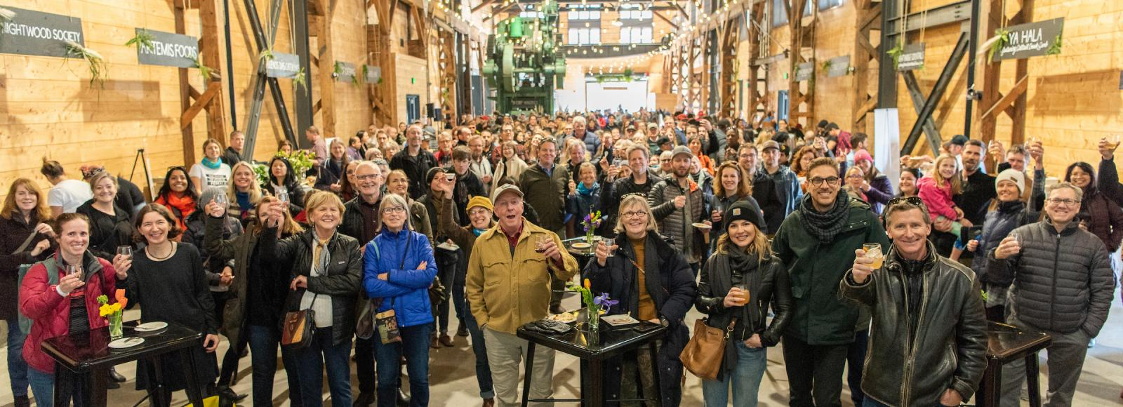 A large group of people raising their glasses in a toast inside a large warehouse.