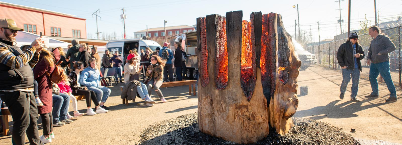 A large upright log on fire outside in an open parking lot