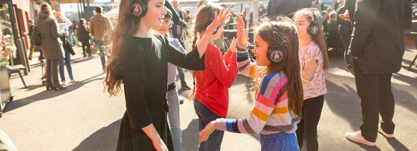 A group of girls wearing headphones play patticakes outside on a bright, sunny day.