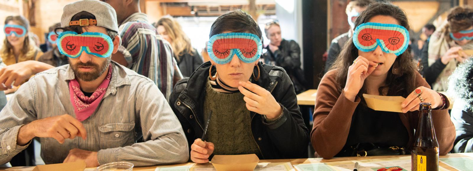 People wearing blindfolds sample food