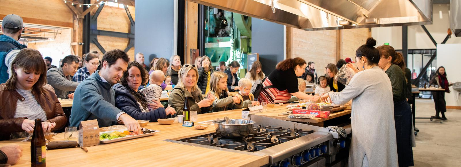 A crowd of people sit at counters watching two women in a large demonstration kitchen