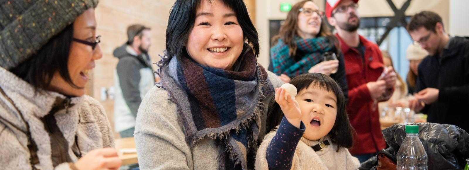 A woman and her daughter smile while enjoying a rice ball.