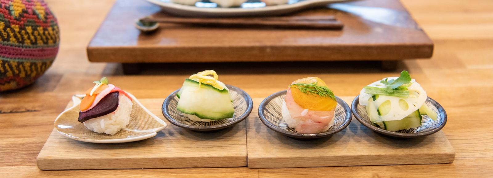 Colorful sushi sits on plates on a wooden counter top.