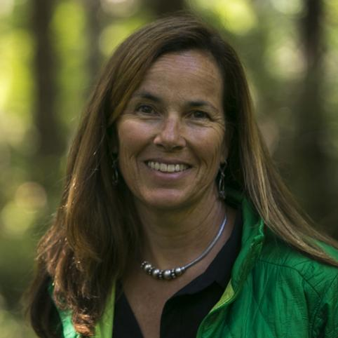 Portrait of SOCAP panelist Bettina von Hagen standing in a forest, smiling, looking directly into the camera, and wearing a green jacket.