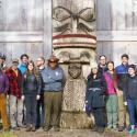 Group of about 20 people, most smiling and looking at camera, standing outside long house next to tall totem pole on a sunny day.