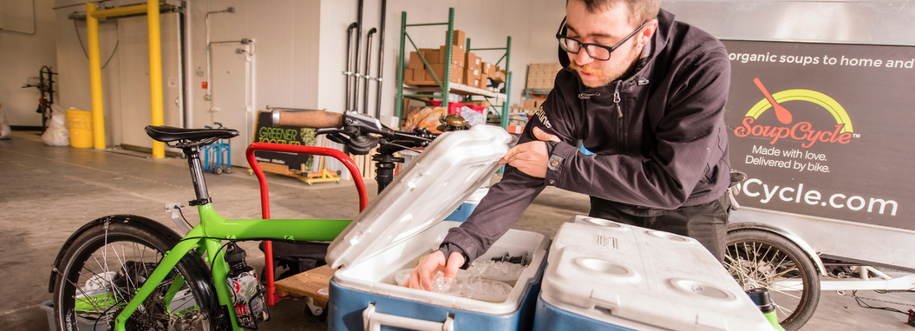 man organizes product in cooler
