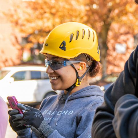 Young woman wearing yellow helmet, safety glasses, and grey sweatshirt smiling