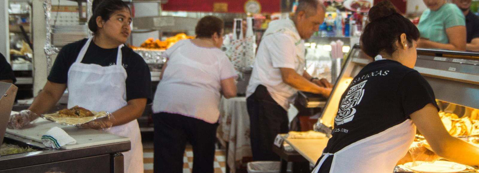 The De León family works with their employees to serve lunch to hungry customers.