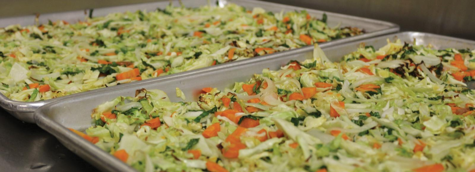 trays of roasted vegetables including cabbage and carrot