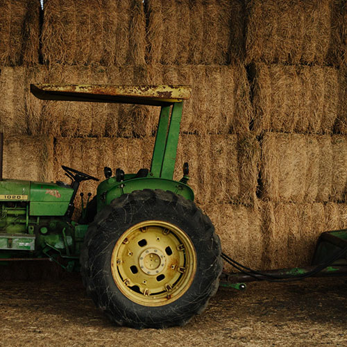 Green and yellow tractor in front of a wall of baled hay
