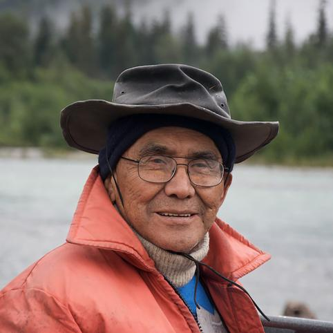 Portrait of an older man wearing glasses, a bucket hat fitted over his beanie, and an orange rain jacket over a knitted sweater