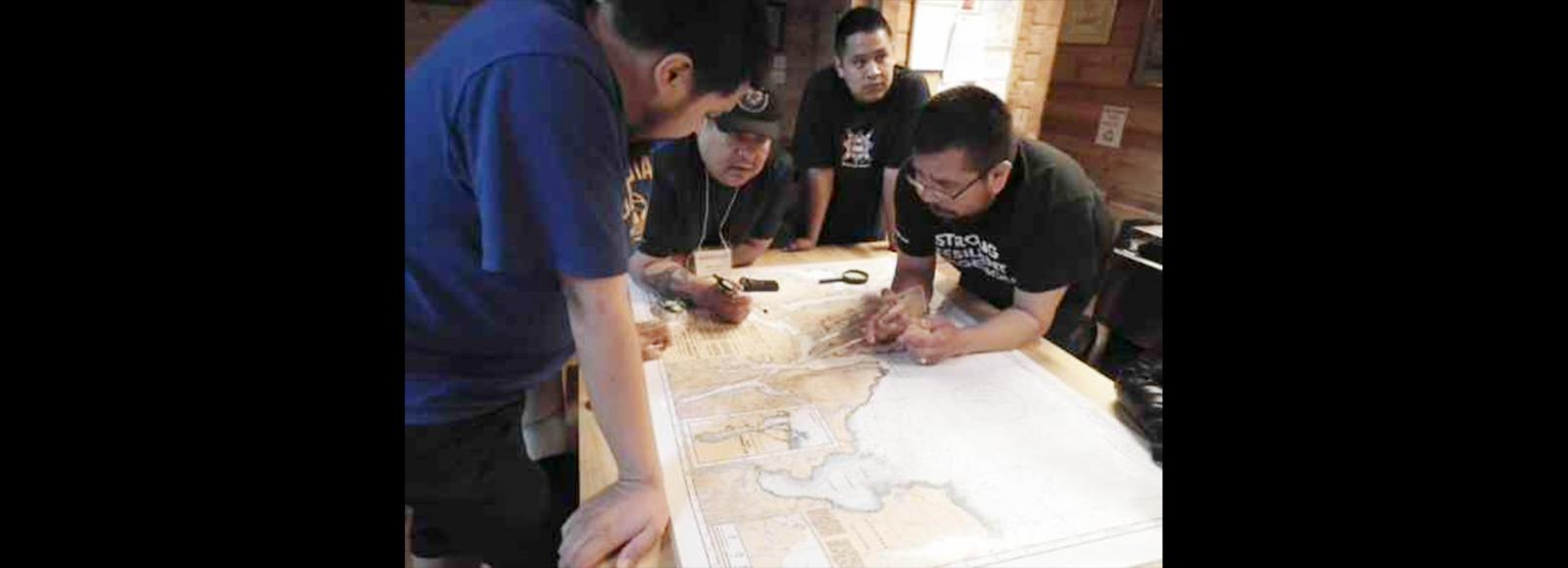 Four men in discussion as they around a map on a table