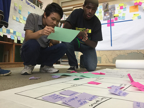 Two students study a large unrolled paper on the floor of a classroom