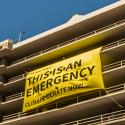 "A large banner with the words ""This is an emergency, climate debate now"" is suspended from the seventh floor of a parking structure."
