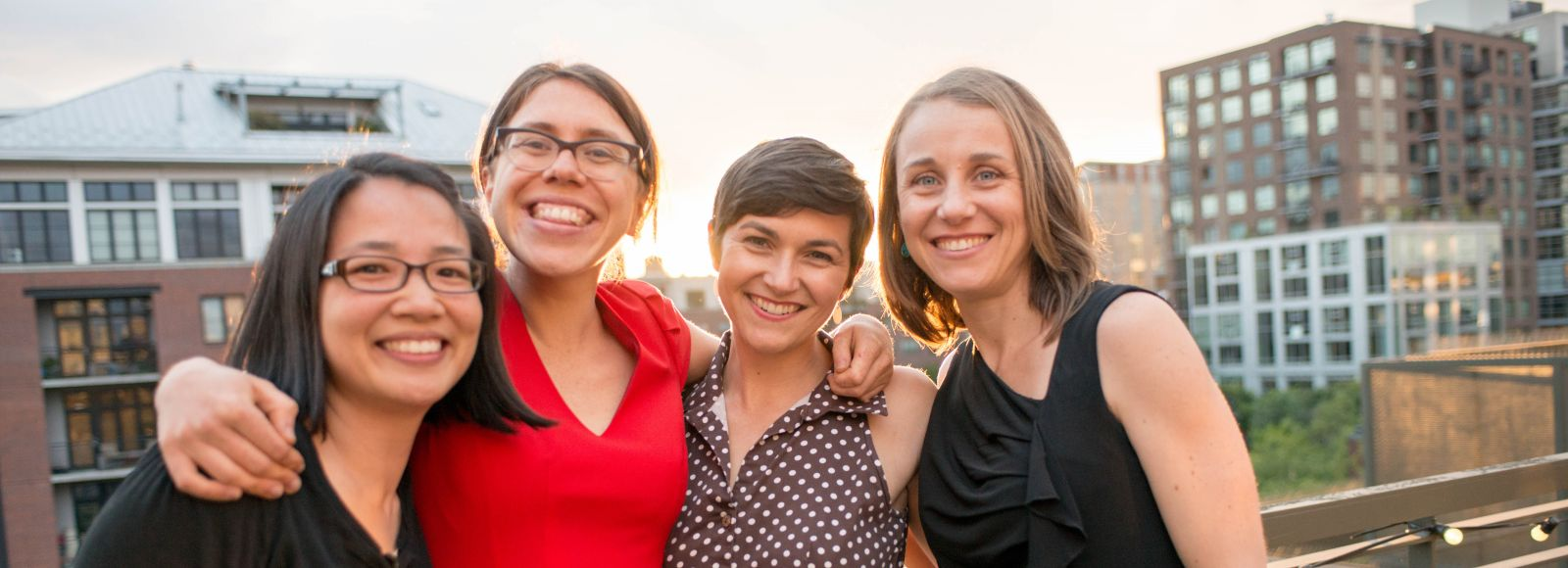 the sun begins to set behind four women standing on a roof with Portland's cityscape in the background