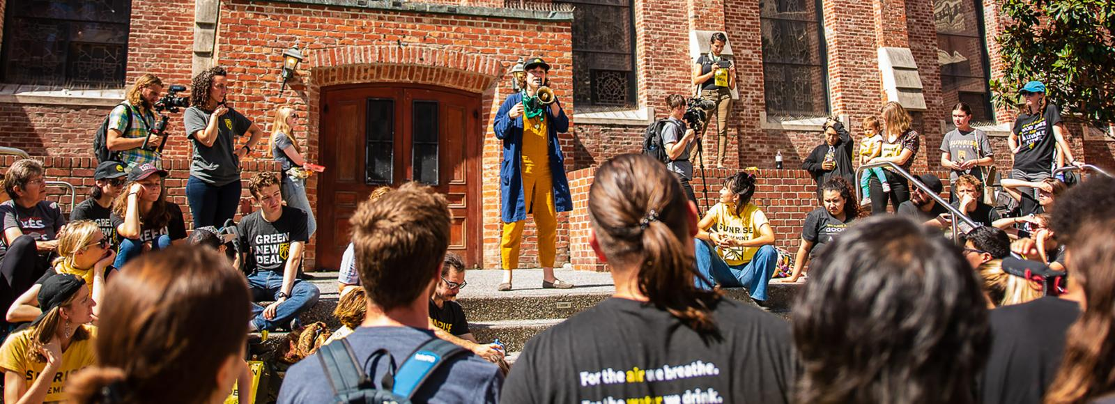 A young person wearing a blue cardigan over a yellow jumpsuit, speaks on a megaphone, to a small crowd of young people gathered in front of a large brick building.
