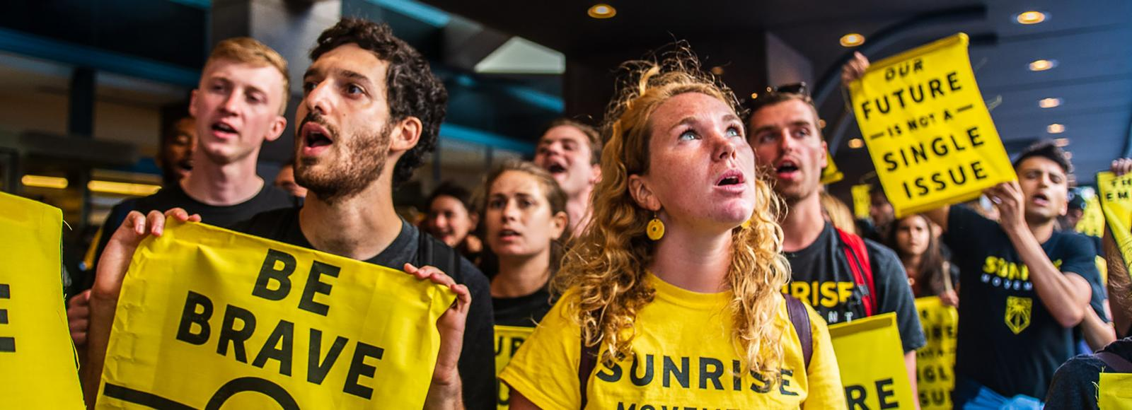 Young people carrying small yellow banners with the words