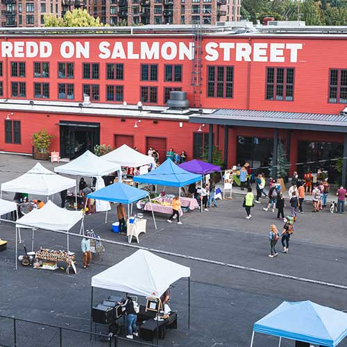 aerial view of a farmers market, grouping of tents, sunny day, red building in background