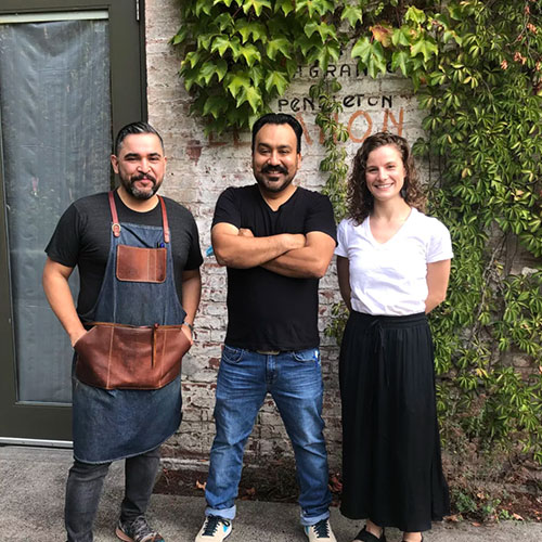 three people in aprons smile in front of ivy-covered brick wall