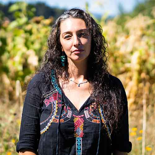 Monique Lopez on her farm, sunny day, looking at camera, small smile