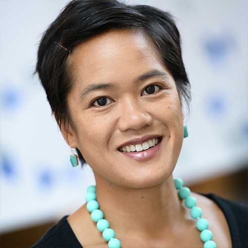 Olivia Rebanal smiles facing the camera. She has short hair and is wearing a necklace of turquoise beads.