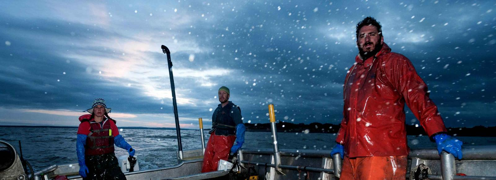 Two men and a woman on a small commercial fishing boat, out on the water under dark skies with flurries of snow.
