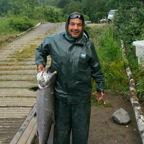 A man wearing a green rain jacket holds up a large, freshly caught salmon that is almost half the length of his standing height. He is standing near a boat ramp leading up to a parking lot just barely visible in the background.