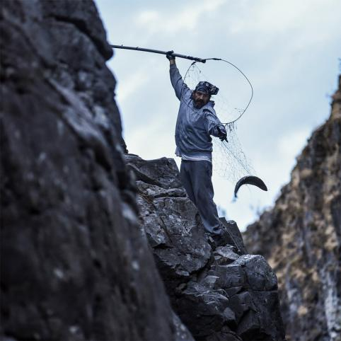 A man holds a fishing net with his right arm extended above his head. With his left arm, he reaches for a fish in the net. He's standing precariously on a rocky crag, with more crags surrounding him.