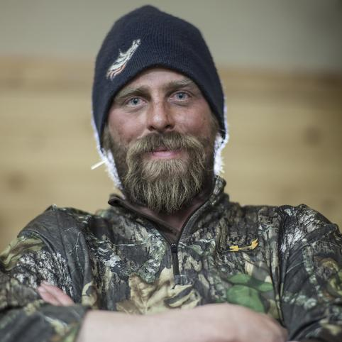 A man with a beard, wearing a black beanie and camo jacket, looking into the camera with his arms folded.