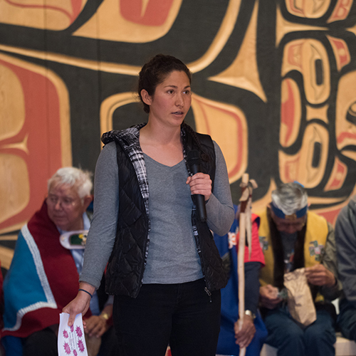 Young woman speaking into a microphone, in front of Native Alaskan artwork on wooden wall, red and black