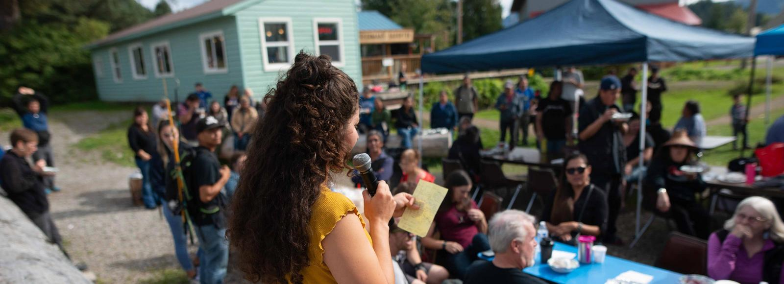 A young woman addresses a gathered community on a sunny day in SE Alaska.