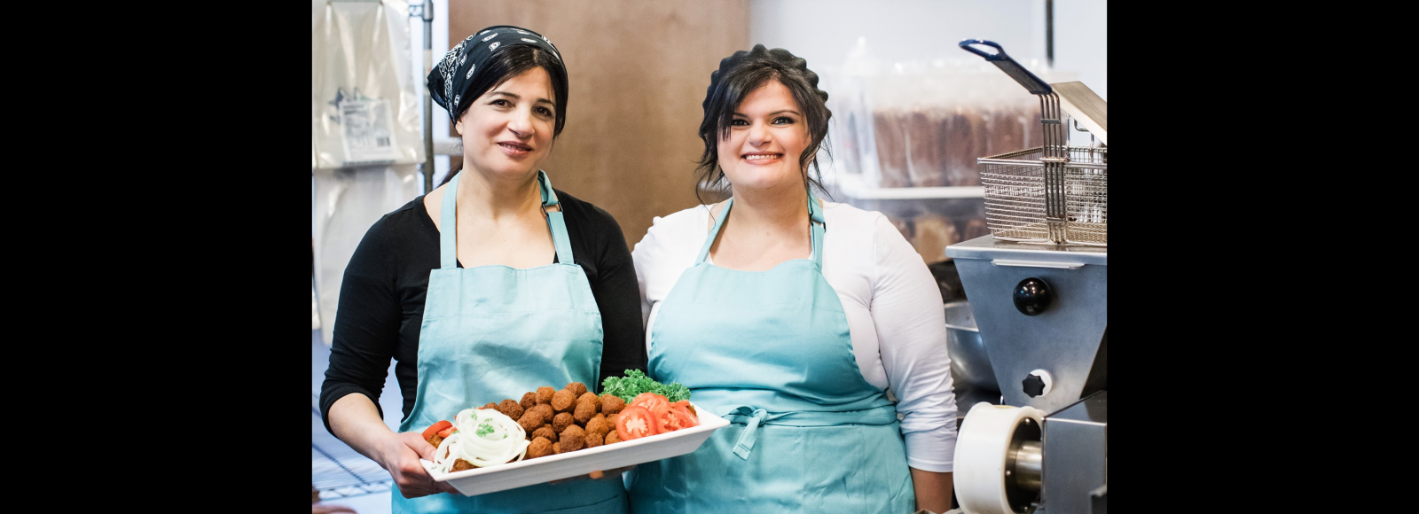 Two women wearing light blue aprons smile at the camera. The woman on the left is holding a platter of falafel.