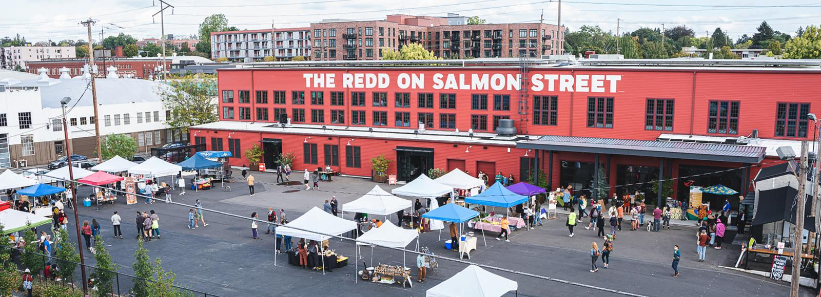 An aerial photo of the Redd on Salmon Street building, with about a dozen EZ-ups arranged in the parking lot. A few dozen customers are scattered across the lot.