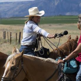 Two women on horseback in a rural setting, one wearing a white cowboy hat and holding a microphone