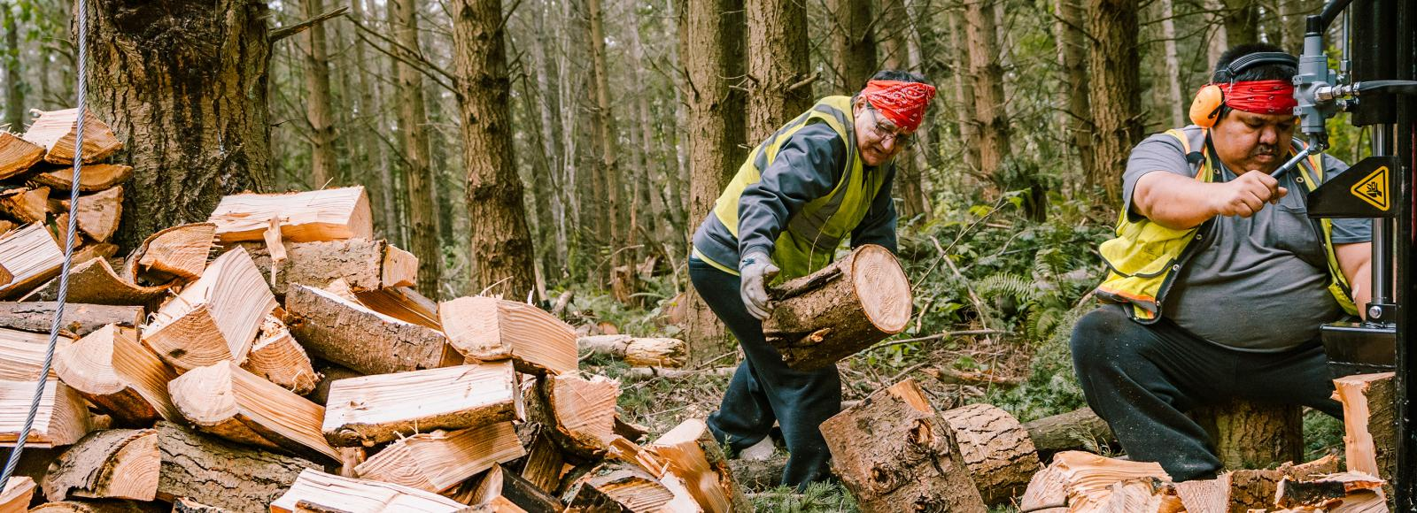A large pile of chopped wood beside two men wearing safety vests. One man is holding a piece of wood, the other man is using machinery to cut the wood.