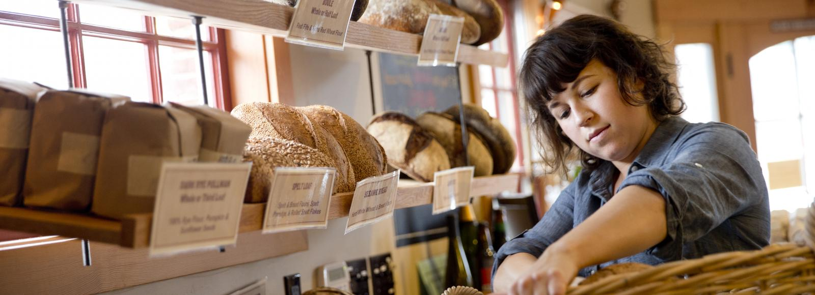 Emily Francis, an employee at Tabor Bread, moves fresh loaves from a basket onto their wooden display racks at the front of the bakery.